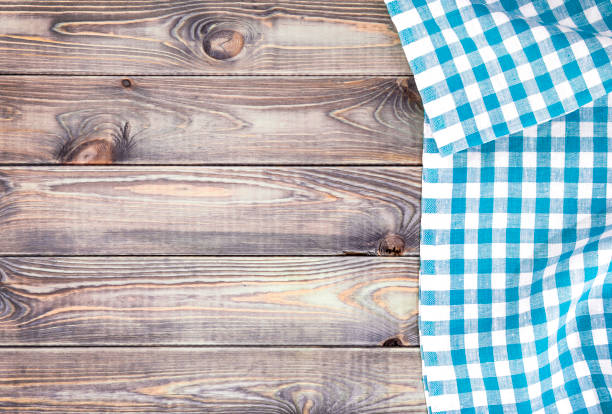 White old wooden table with blue checkered tablecloth, top view with copy space - foto stock