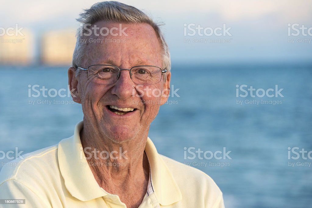 A white, older man grins in front of a body of water.  royalty-free stock photo