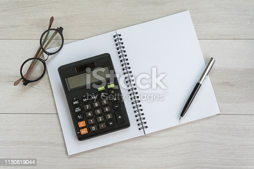 istock White opening blank paper note book with pen, calculator and eyeglasses on light grey wooden table background with copy space using as finance, debt and budget plan 1130819044
