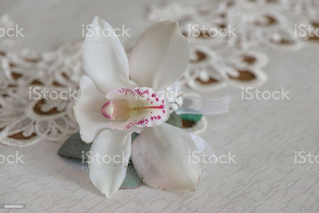 Ramo de orquídeas blancas bouquet pequeño para ojales utilizado para novios e invitados de la boda se coloca en un paño blanco, en luz natural. - foto de stock