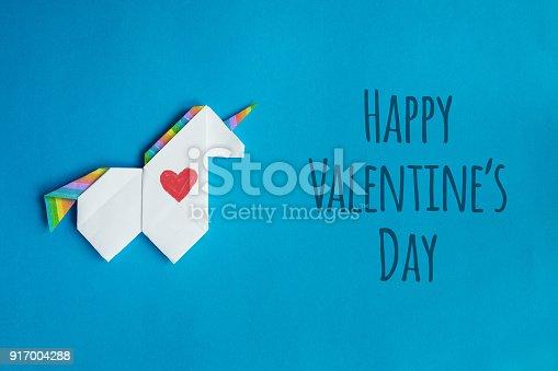 White origami unicorn on blue background