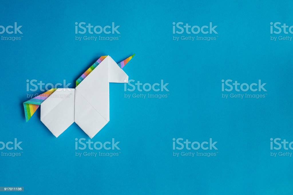 White origami unicorn on blue background stock photo