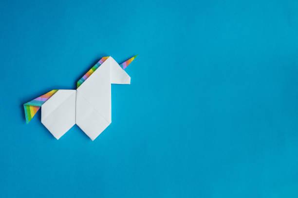 White origami unicorn on blue background stock photo