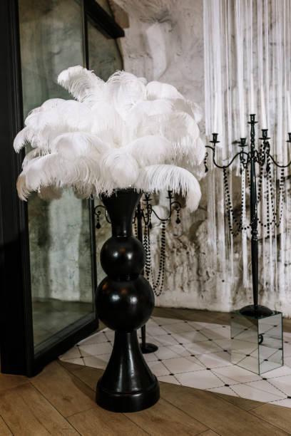 weißen straußenfedern in schwarzer vase, hochzeit dekoration details - hochzeits thema hollywood stock-fotos und bilder