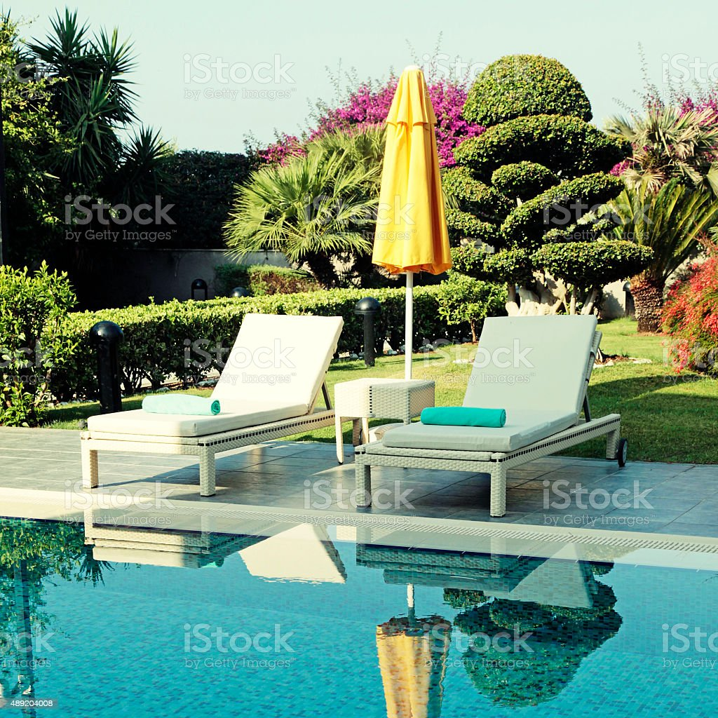 white outdoor furniture and yellow umbrella near resort swimming stock photo