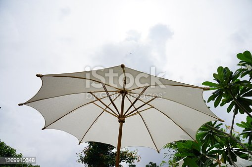 Opened large White umbrella on sky background.