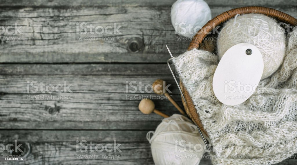 White oval label on wool threads roll to basket with knitting and...