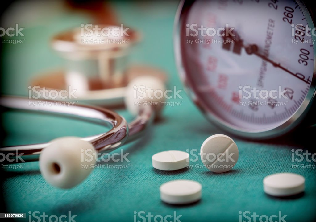 White pad next to a manometer to measure blood pressure and a stethoscope in a hospital, conceptual image stock photo