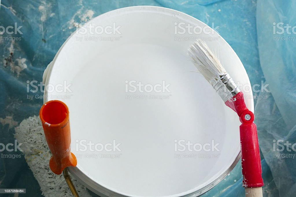 white paint bucket and brush paint roll beside,