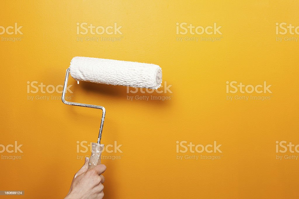 White Paint Roller Against Orange Wall stock photo | iStock