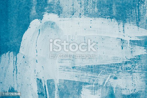 istock White paint stains on blue canvas. Drips of white paint on the blue wall. Painted dirty concrete wall. Smeared wall in whitewash, stained plaster. Abstract pattern of spotted white stucco. 1157292846