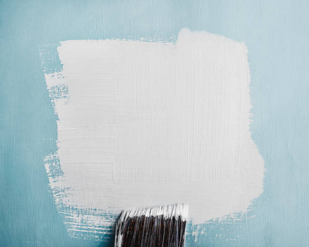 White paint swatch painted on blue wall stock photo