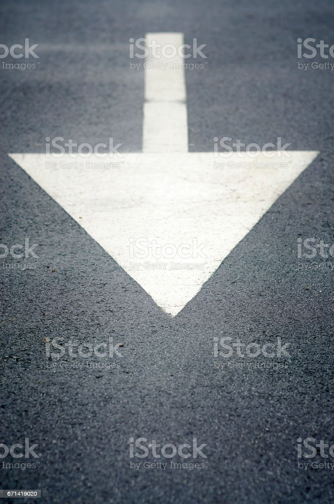 White painted direction arrow sign on the road stock photo