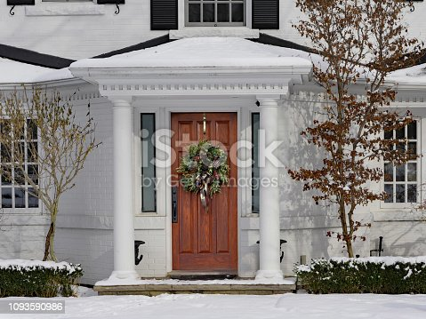 white painted house in winter with Christmas wreath