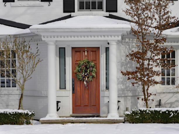 weiß lackierte haus im winter mit weihnachtskranz - deko hauseingang weihnachten stock-fotos und bilder
