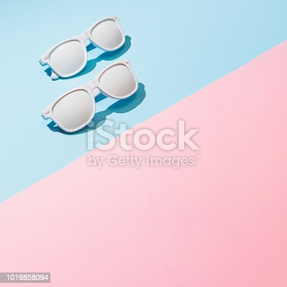 istock White painted sunglasses with pastel pink and blue background. 1019858094