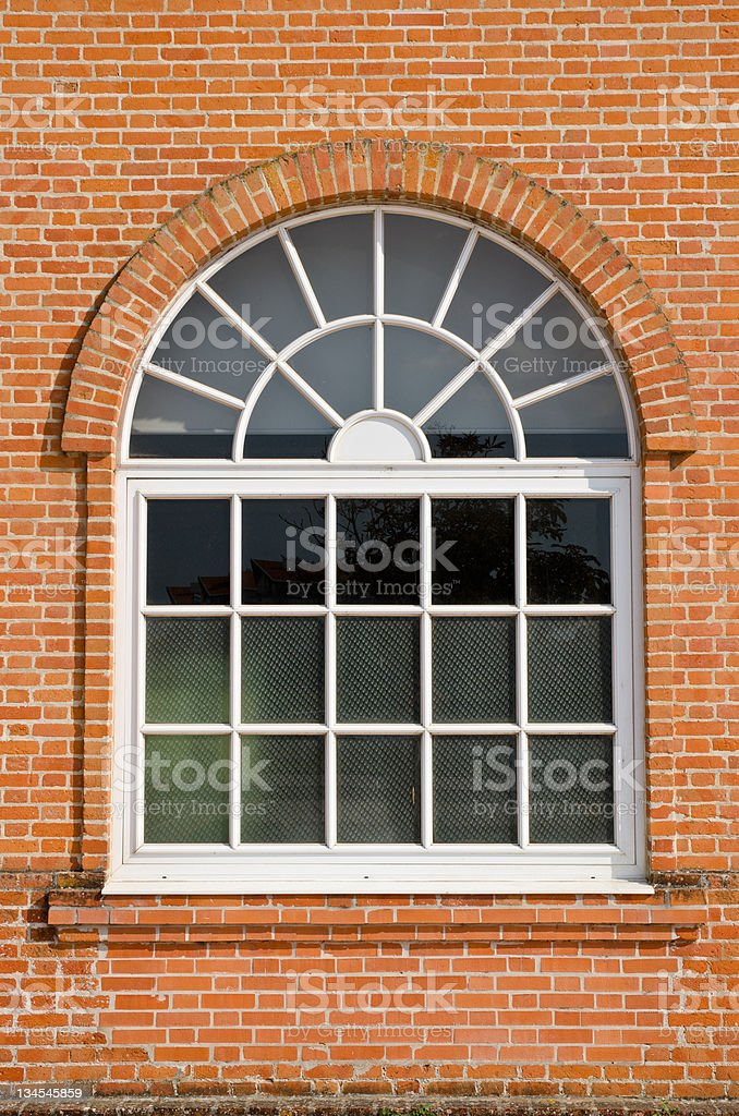 White painted wood arched window in brick wall stock photo