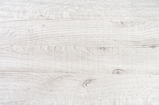 Rough white painted wooden panel composed of four planks. All boards have a clear texture of wood. Scratches, cracks and other damages are strongly expressed. Some of them contain wood knots. A wood grain pattern featuring even grains of wood running horizontally across the image.