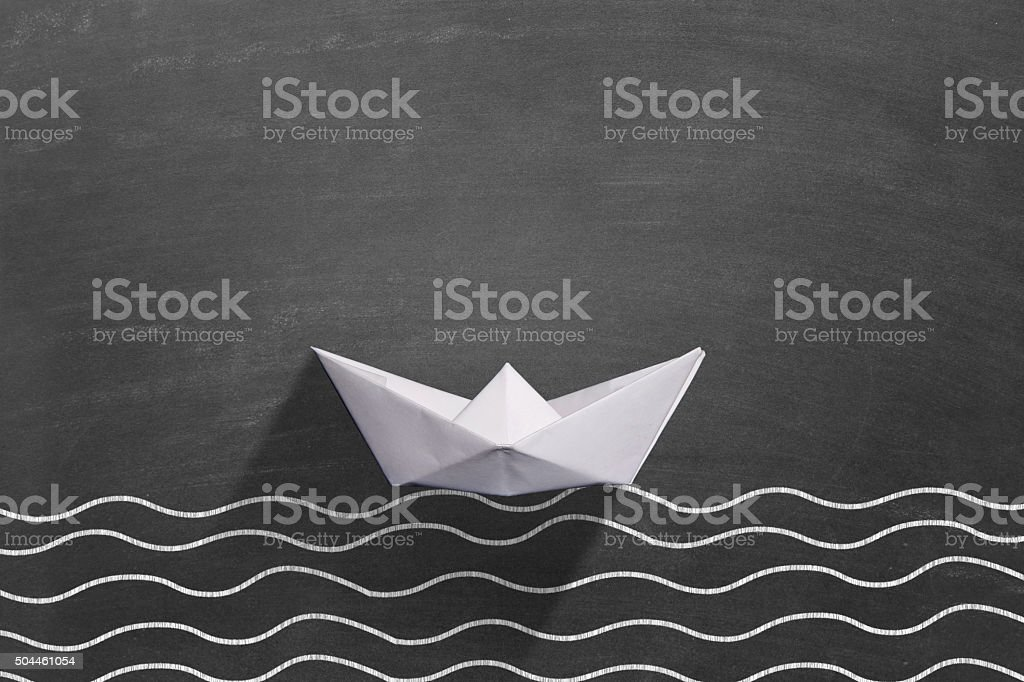 White paper boat floating on water stock photo