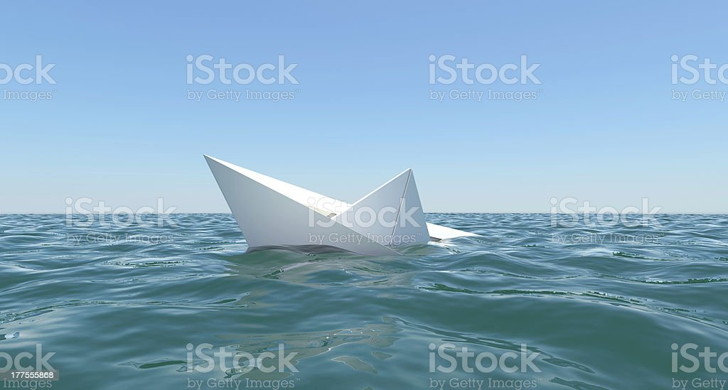 White paper boat is sinking in the sea water stock photo