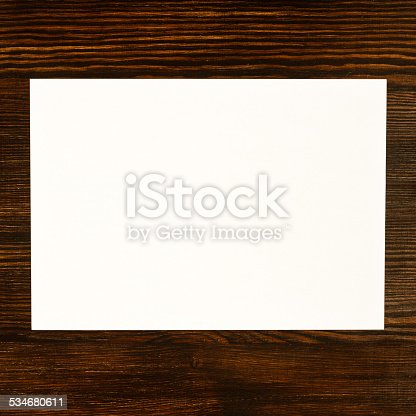 istock White paper card on wooden desk background 534680611