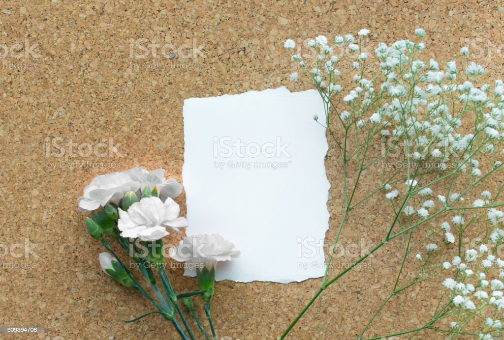 White paper card with flower on wooden corkboard background.Flat lay.feminine concepts design. stock photo