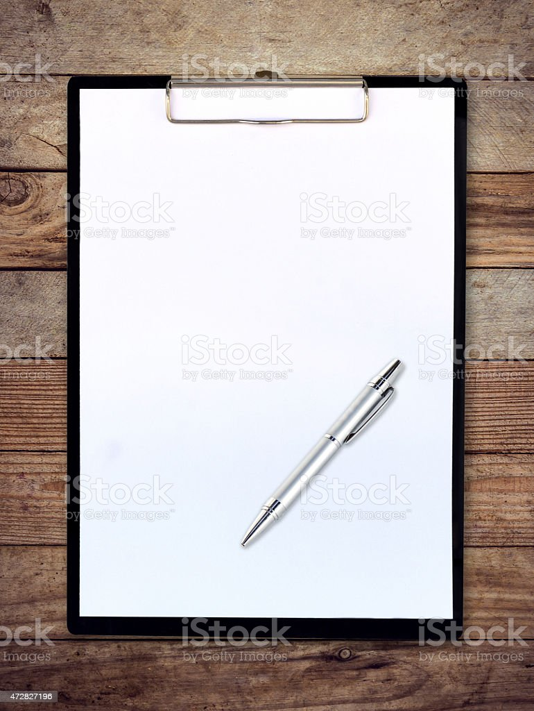 white paper clipboard on wood background with pen stock photo