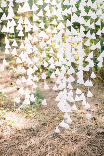 white-paper kegel elemente aufgereiht auf thread als teil einer hochzeit dekor, im freien - eheringe öko stock-fotos und bilder
