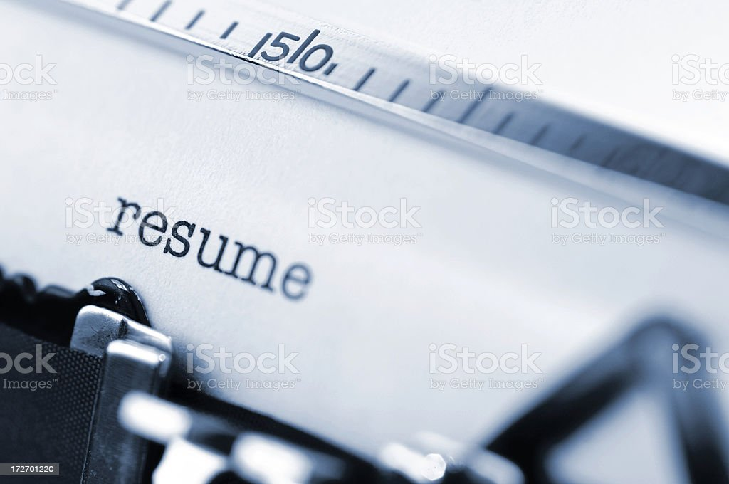 White paper in a typewriter with the word resume typed. stock photo