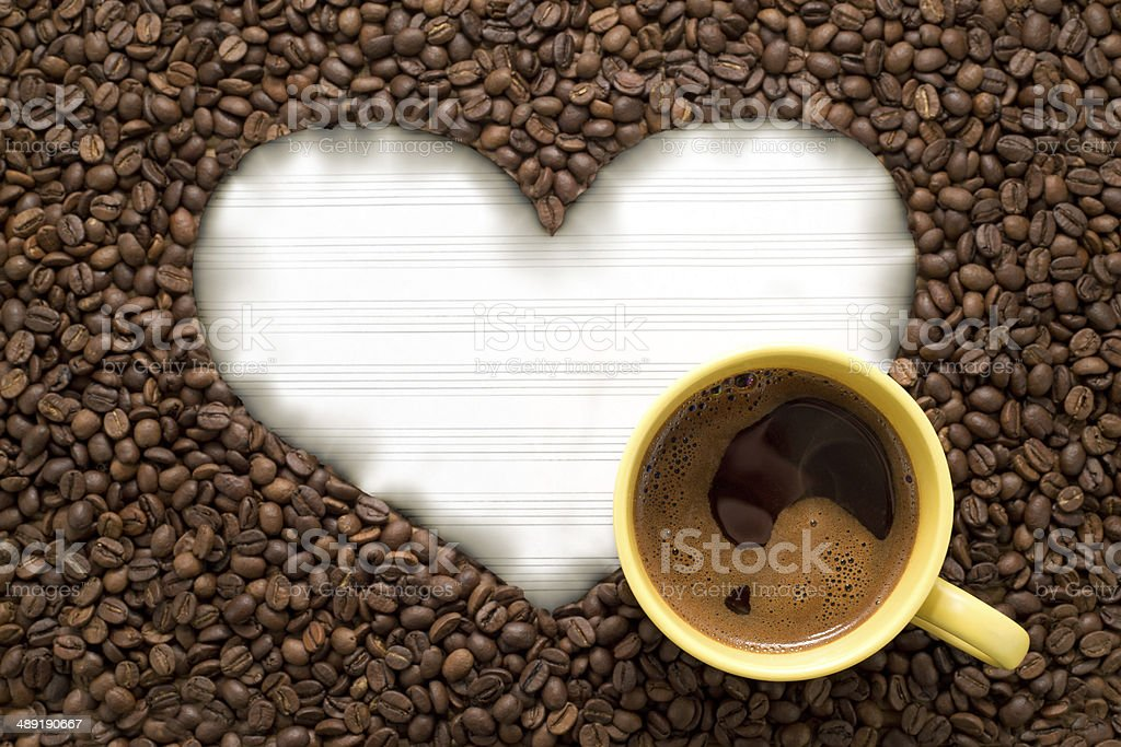 White paper in heart shape with yellow cup of coffee stock photo