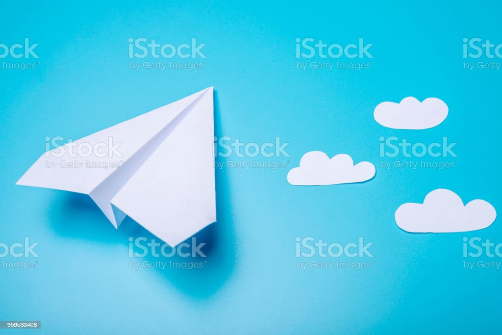 White paper origami airplane lies on pastel blue background stock photo