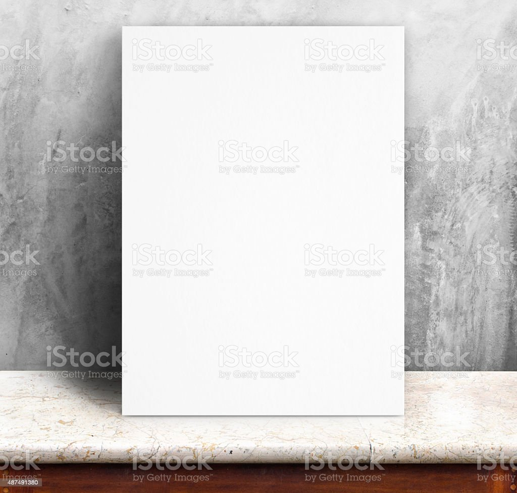 White paper poster lean at concrete wall and marble table stock photo