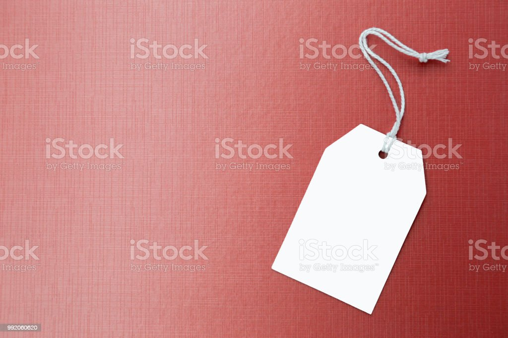 White paper price tag on red texture background, business background...