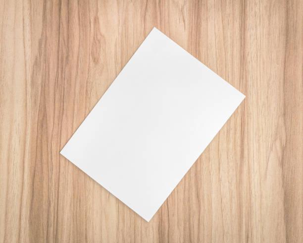 weißes papierblatt auf hölzernen hintergrund. vorlage a4 dokument und leeren platz für text. - karten wandkunst stock-fotos und bilder