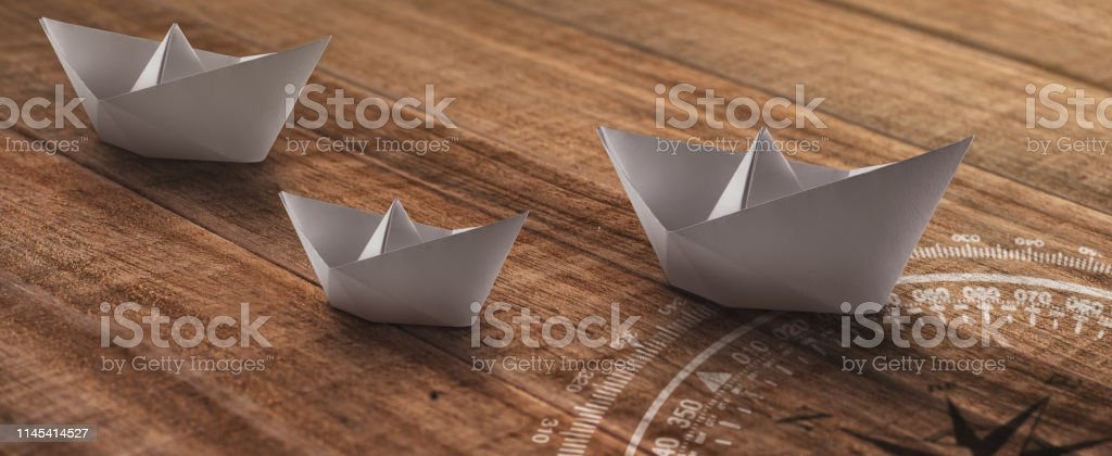 White paper ships on a wooden rustic background moving towards one...