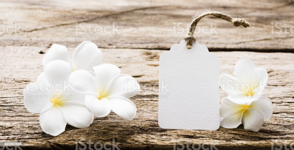 White paper tag label decorate with plumeria flowers on rustic wood...