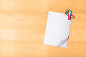 White paper with clip and ribbon with rainbow flag