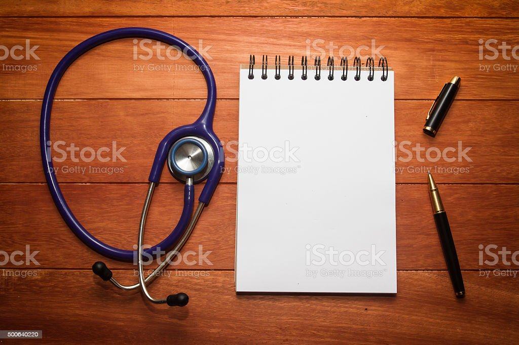 white paper with stethoscope and pen. stock photo