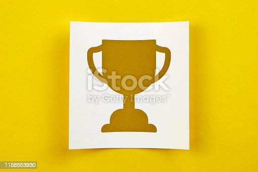 544347868 istock photo White Paper With Winner Trophy Symbol On Yellow Background 1158553930