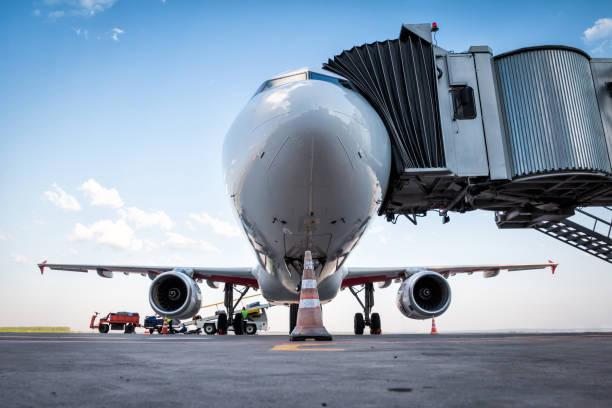 Ein weißes Passagierflugzeug an der Jetbrücke und wird mit Gepäck beladen – Foto