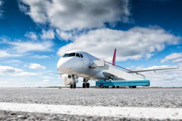 Weiße Passagierflugzeug mit Treppe-Auto auf dem Flughafen-Vorfeld – Foto
