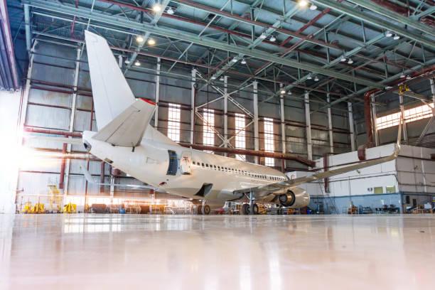 Weißes Passagierflugzeug im Hangar bei der Morgenbeleuchtung. Überprüfung mechanischer Systeme für den Flugbetrieb. Flugzeug in Der Wartung – Foto
