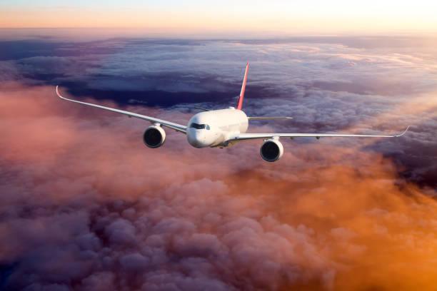 White passenger airplane in the sunset sky. stock photo