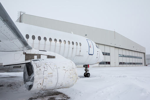 White passenger airplane near the aircraft hangar in cold winter weather. The jet plane needs repair