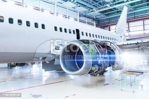 White passenger aircraft under maintenance in the hangar. Repair of airplane engine on the wing and checking mechanical systems for flight operations