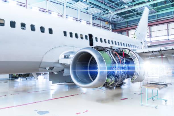 Weißes Passagierflugzeug in Wartung im Hangar. Reparatur des Flugzeugtriebwerks am Flügel und Überprüfung mechanischer Systeme für den Flugbetrieb – Foto