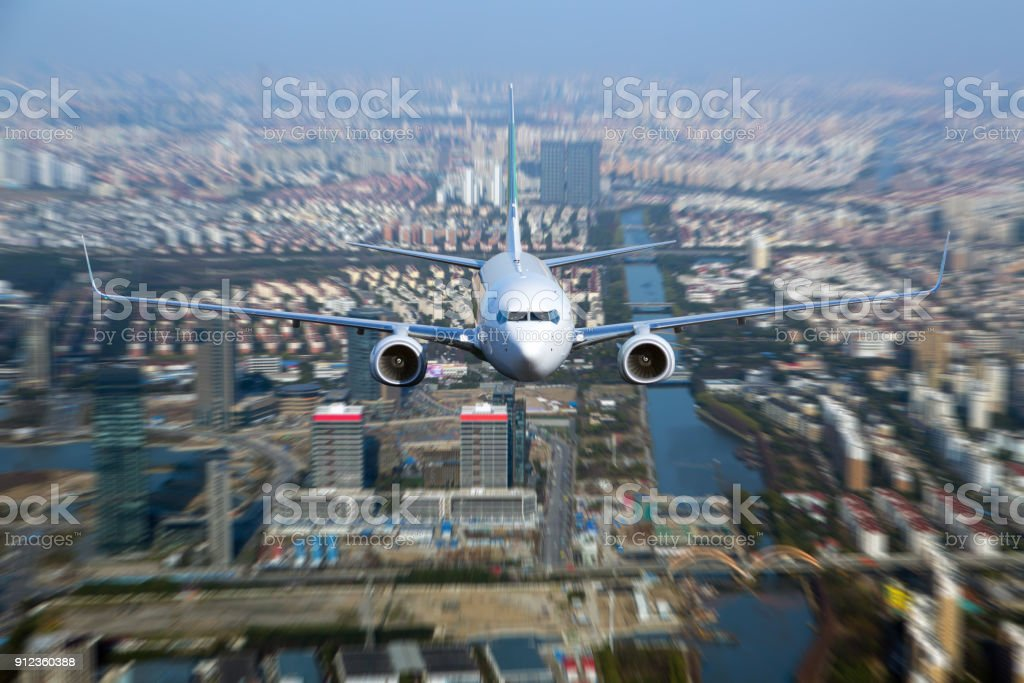 White passenger plane flyes above the city. stock photo