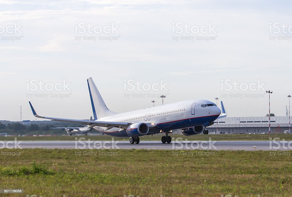 white passenger plane take off away from airport stock photo