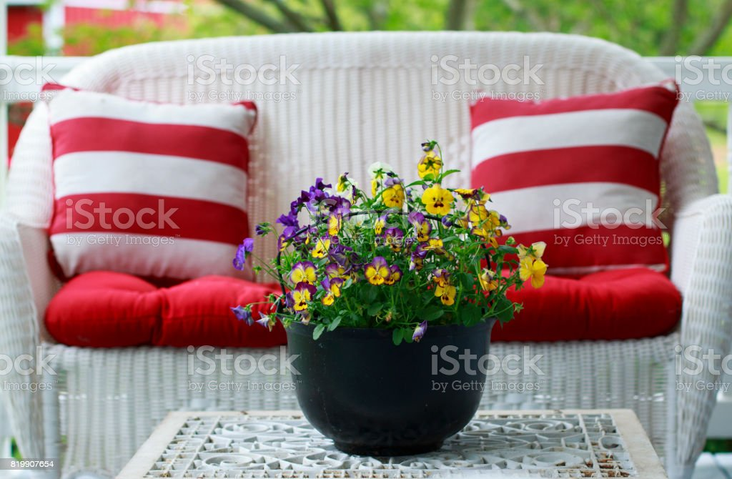 White Patio Furniture and Colorful Pansies in a Black Metal Bucket