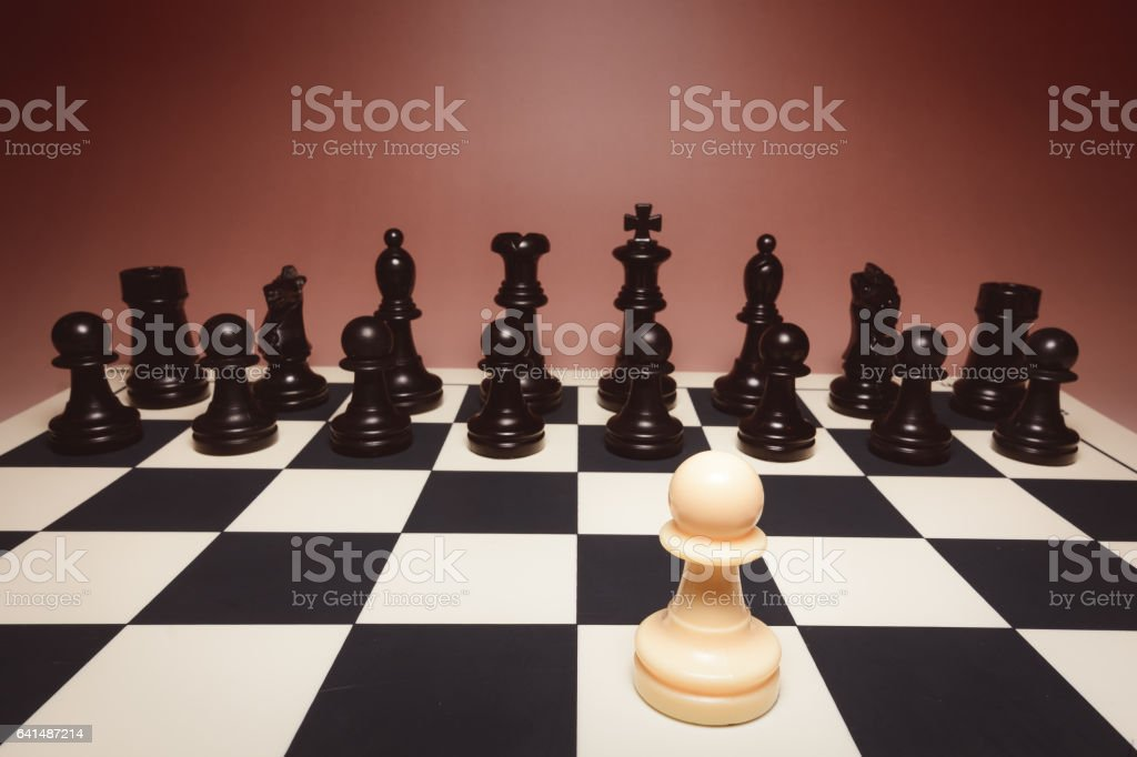 White Pawn against black pieces in chess board stock photo